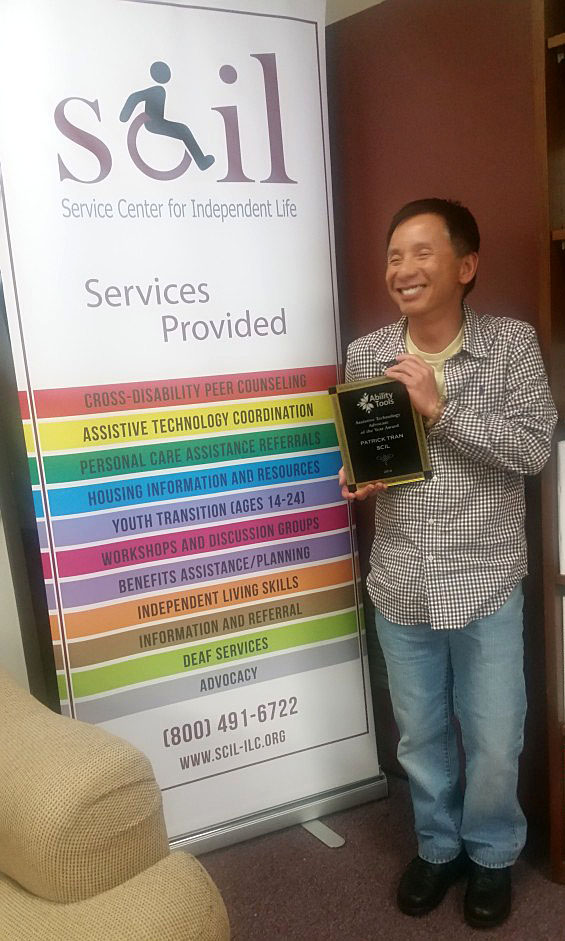 Assistive Technology Coordinator, Patrick, holding his award for AT advocate of the year